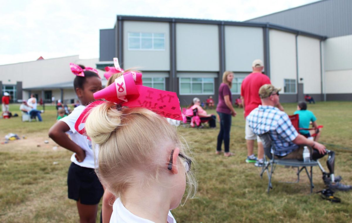 The cheerleaders for the Boys & Girls club football team sport Breast Cancer Awareness themes bows for this month.