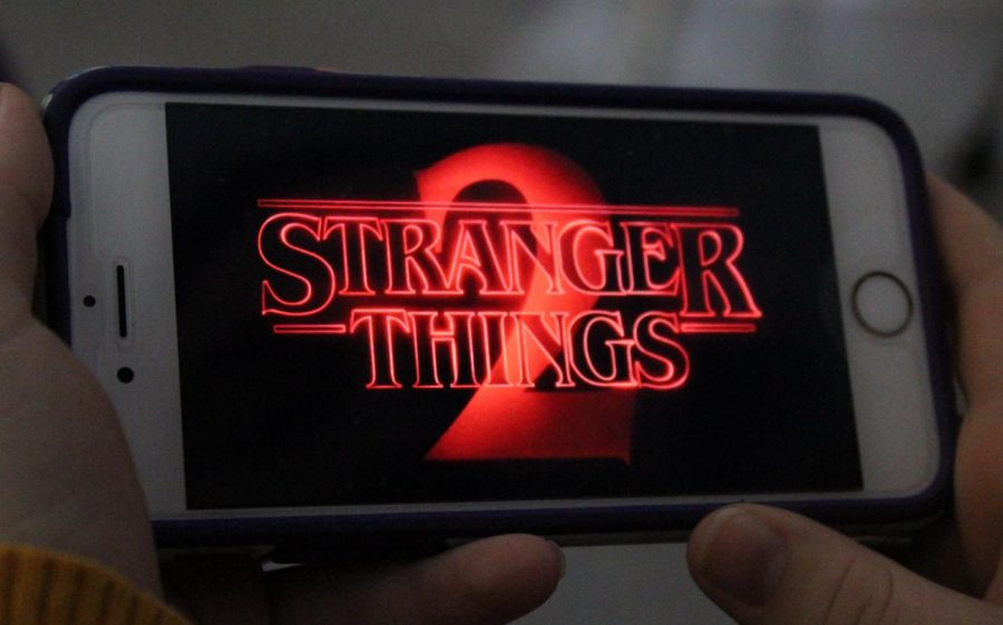 A student watching Stranger Things 2 on their phone