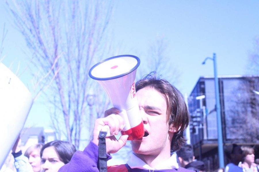 Leading the crowd, sophomore and march organizer Huxley Richardson speaks into a megaphone. Demonstrators chanted in support of stricter gun control.