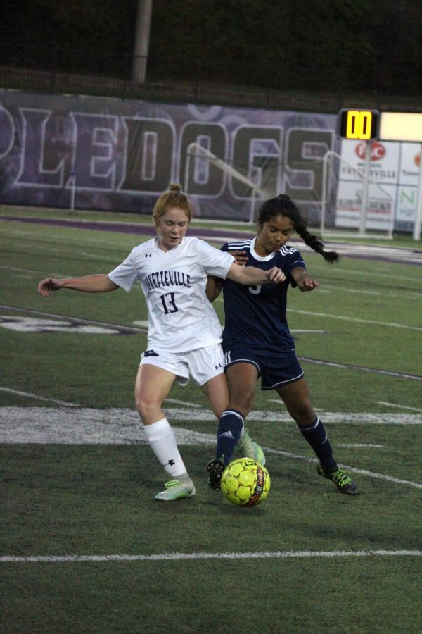 Morganne Browning (10) defends and takes the ball, trying to pass to a forward.
