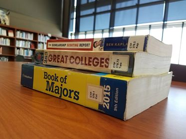 A pile of books sitting on a table that have useful information in them about college.