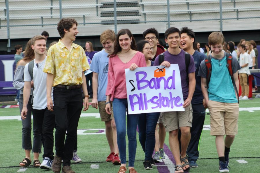 Band All-state smiles as they walk down the middle of the field.