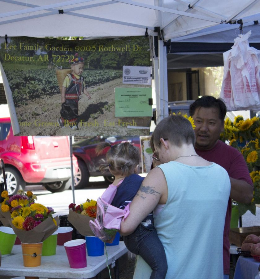 A woman and her daughter talk to a local vendor about his colorful bouquets, enjoying the lovely late summer weather.
