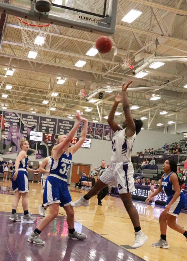 Jumping over the Rogers defender, Hatiana Releford (9) grabs the rebound.