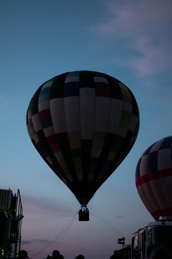 A hot air balloon floats above the festival in the evening. Tethered rides were offered exclusively before sunset, due to the morning's rain.
