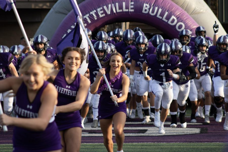Senior cheer members Madeline Graves, Kennedy Johnson, Abby Ross, and Kennedy Combs (not pictured) carry flags to lead the varsity Fayetteville football team onto the field.