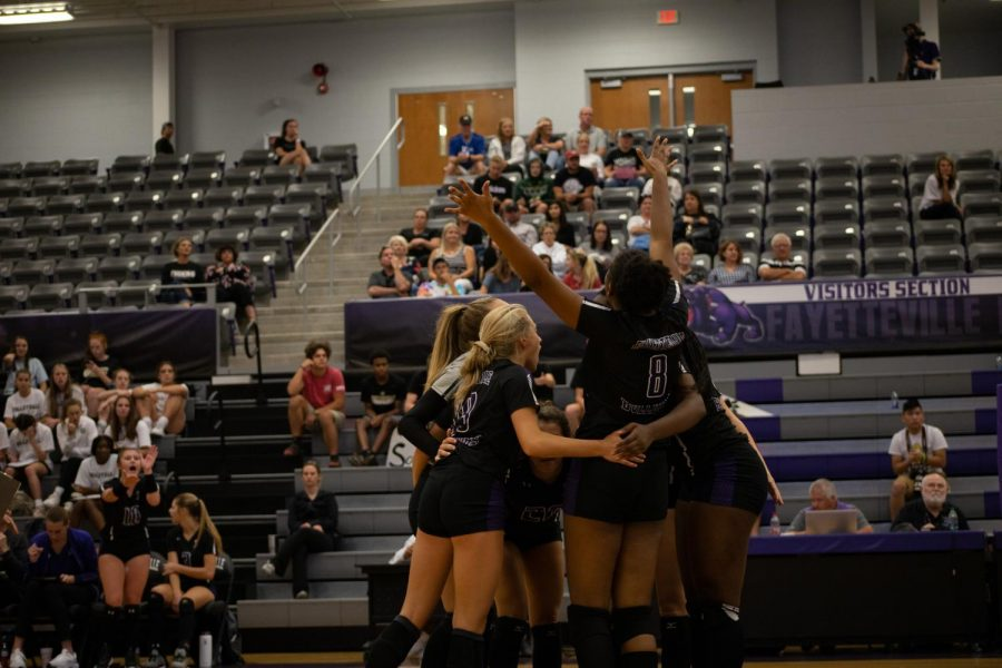 After fighting for the point, Junior Rosanna Hicks throws her hands up in celebration while receiving a hug from her teammates.