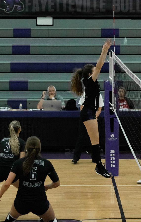 Perry Flannigan (11) and Madison James (12) back up Amelia Whatley (12) as she jumps to block Rogers' serve.