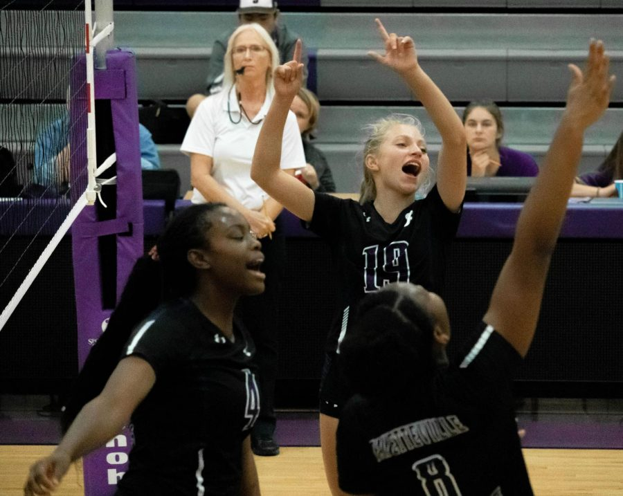 One point closer to the win, Kennedy Phelan (9), Arianna Walter (12), and Rosana Hicks (11) celebrate during the third set.