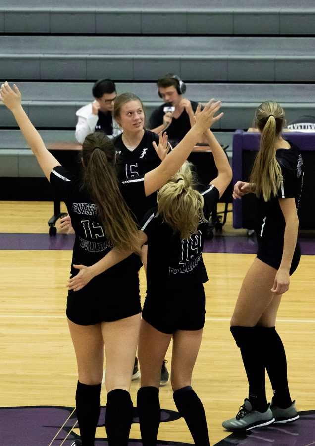 Celebrating a point, Kennedy Phelan (9), Amelia Whatley (12), Perry Flannigan (11), and Madison James (12) gather in the middle of the court.