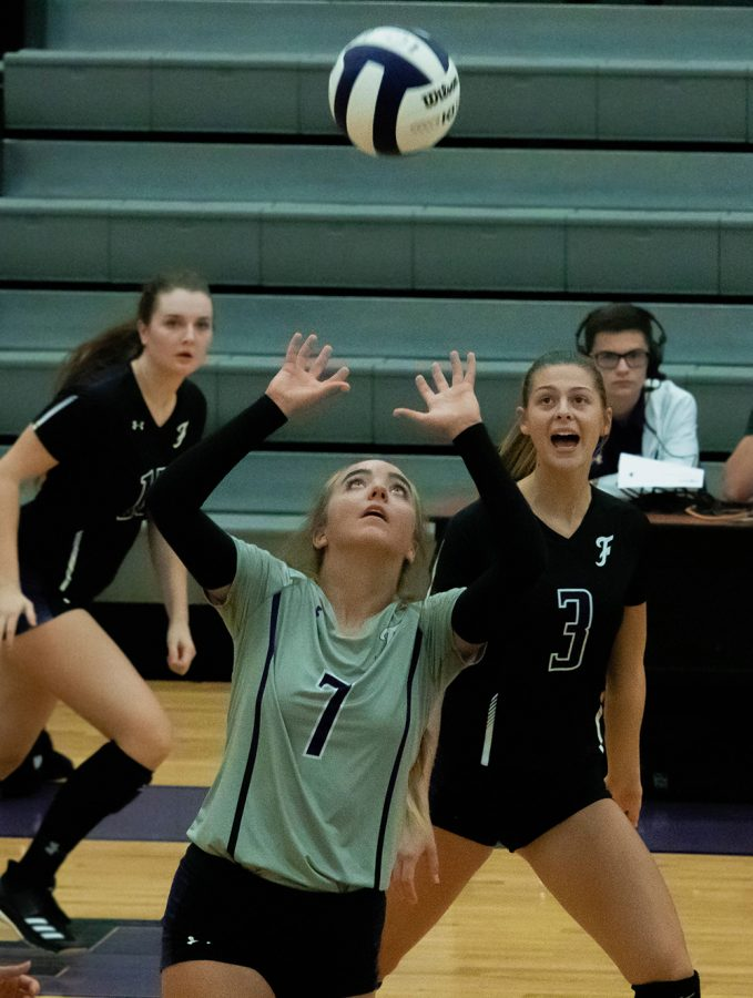 Junior Gracyn Spresser prepares to set the ball while Seniors Madison James and Amelia Whatley watch from behind.
