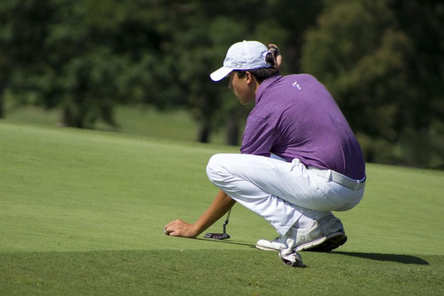 Lining up his putt, William Whitelaw (12) crouches down to get a better view of the green.
