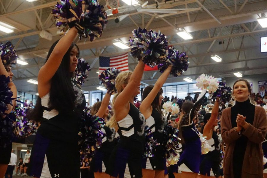 The cheerleader proudly preforming for the student section at the pep rally for homecoming as their coach walks by.