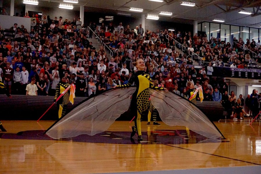 Color Guard preforming at the Halloween pep-rally for the senior section while the crowds cheered.