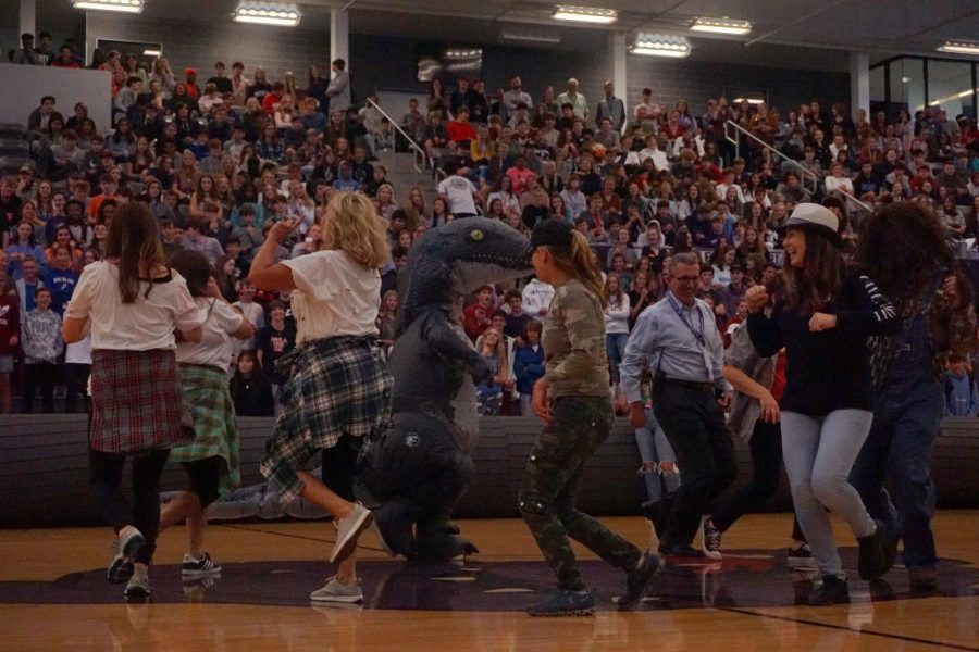 Assistant Principal Mr.Gheen  and teachers Dancing in a circle at the pep-rally while they all laugh.