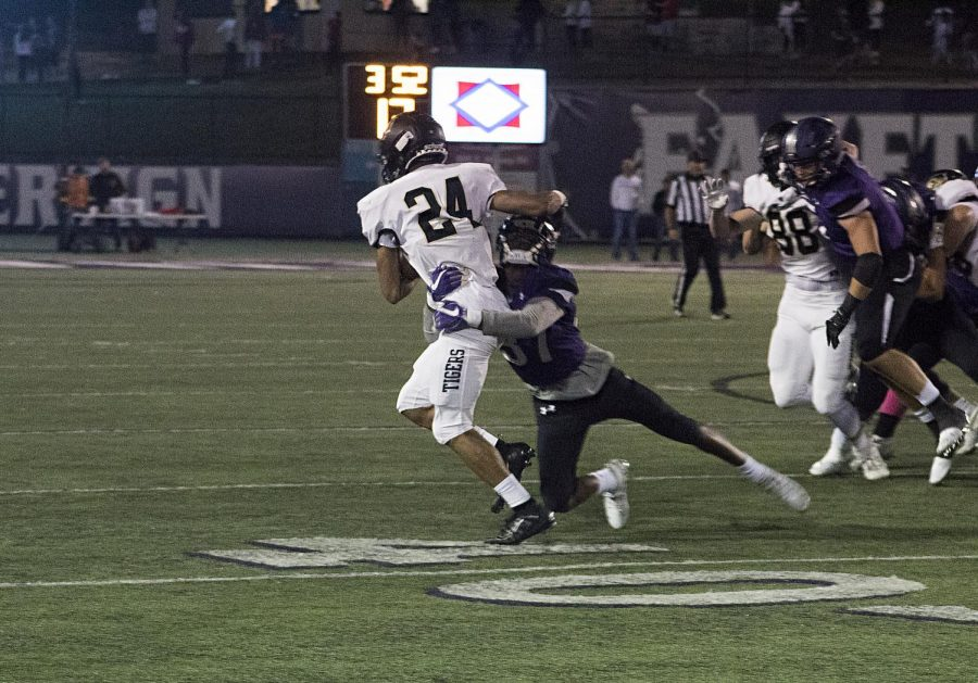 Sophomore Braelon Palmer grips onto player 24 in an attempt to stop his way to the endzone.