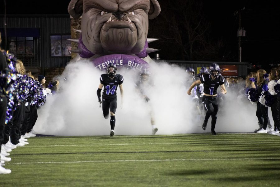 The varsity Fayetteville football team run onto the field through fog and lines of cheer and dance members.