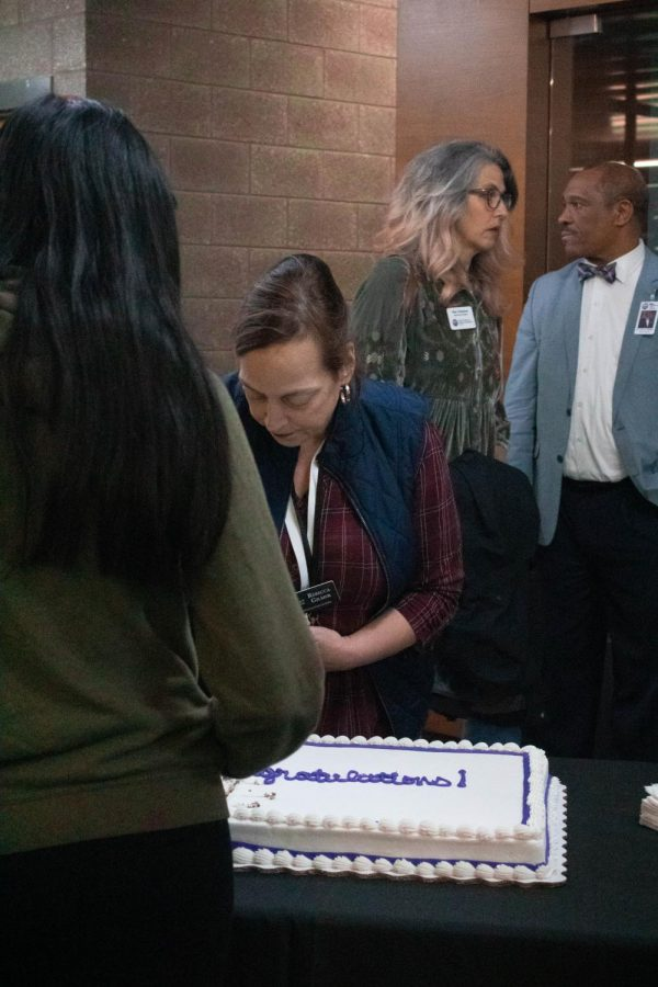 Ramay Junior High school teacher Rebecca Gilmer serves cake at the reception for the ESL exit ceremony in the FHS cafeteria.