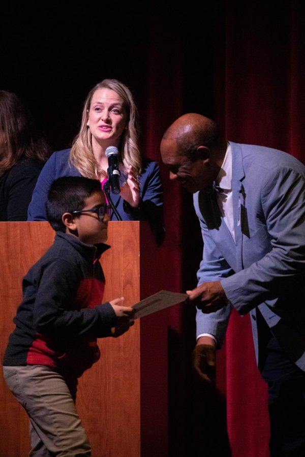 Happy Hollow Elementary student Jayden Lopez accepts his exit certificate from Fayetteville Public Schools Superintendent Dr. Colbert. The exit ceremony was from 6-8pm in the FHS Performing Arts Center.