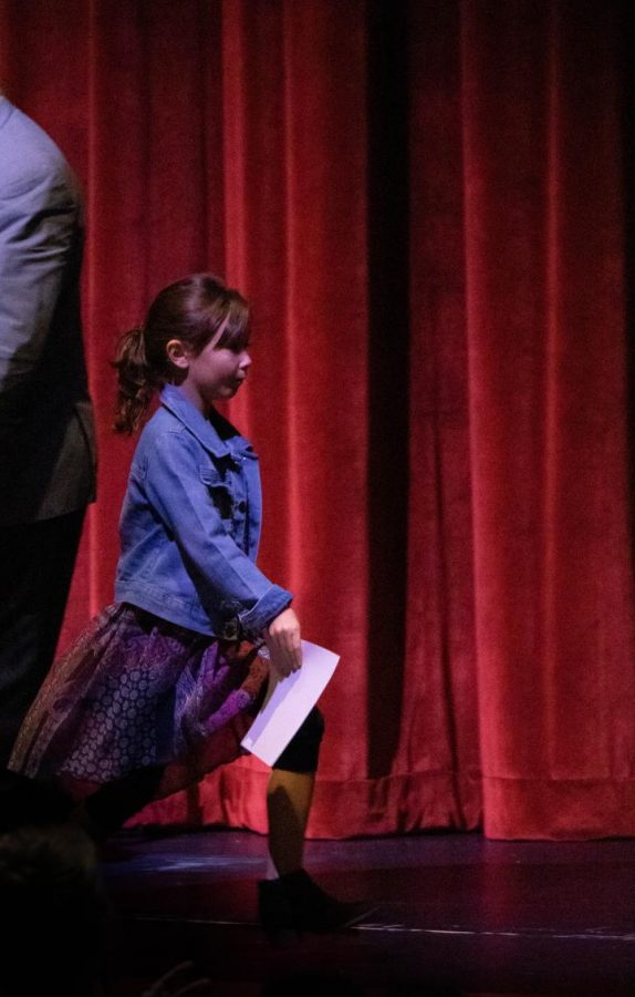 Root Elementary School's Emily Yale walks across the PAC stage after receiving her certificate. Yale was the only student to be celebrated for exiting ESL from Root.