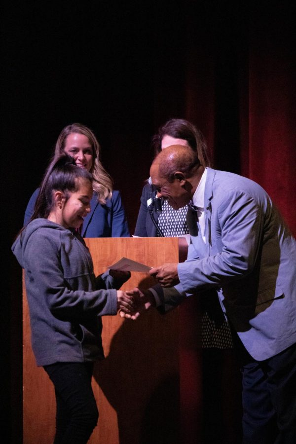 Amarely Mendez from Ramay Junior High shakes Dr. Colbert's hand as she is presented with her certificate. Before the exiting students walked the stage, Dr. Colbert spoke about how important it is for students to continue speaking their native language and to realize that it is a significant part of who they are.