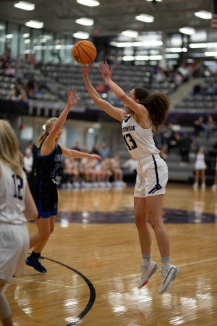 Aiming for a three point basket, Sasha Goforth (12) jumps above the rogers defender.