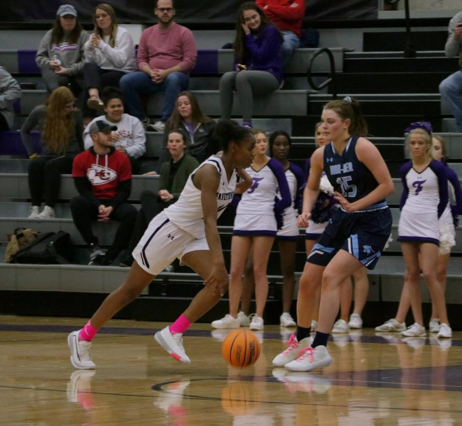 Coriah Beck (12) dribbles the ball toward Fayetteville's side of the court.