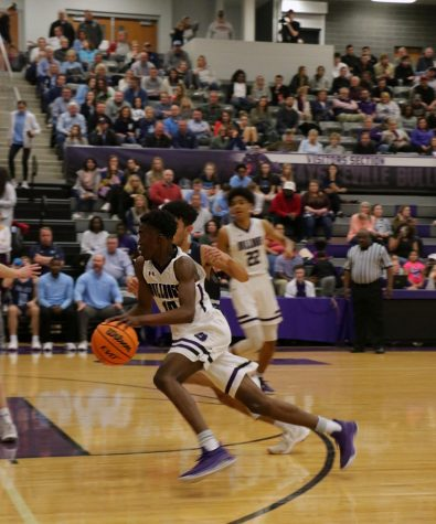 Sophomore Landon Glasper swerves past a Har-Ber player while dribbling the ball to make basket.