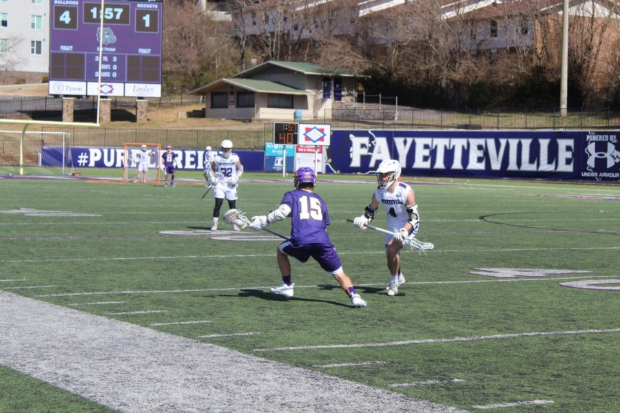 Fayetteville player charges at an offensive rocket player.