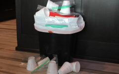 A trashcan sits overfilled with Styrofoam products.